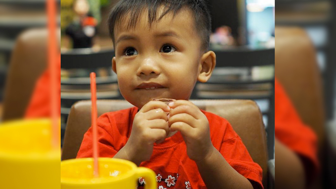 toddler boy with beverage in front of him