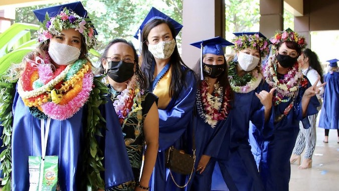 graduates with blue gown wearing lei and masks