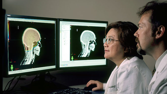 two researchers looking at brain scans