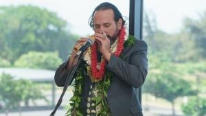 man playing nose flute