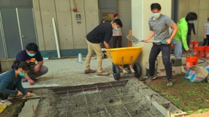 people help to create a concrete ramp