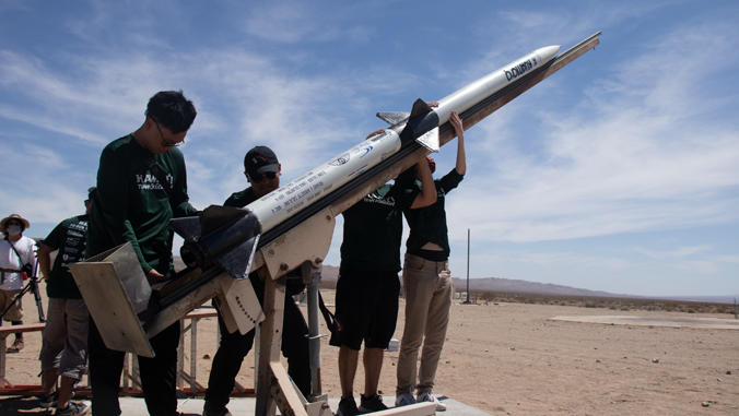 people standing prepping a rocket to launch