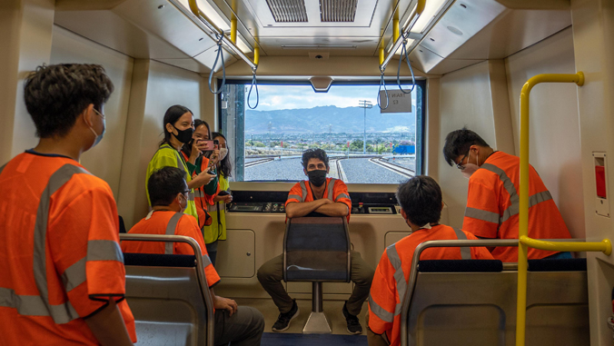 people sitting in a rail car with vests on