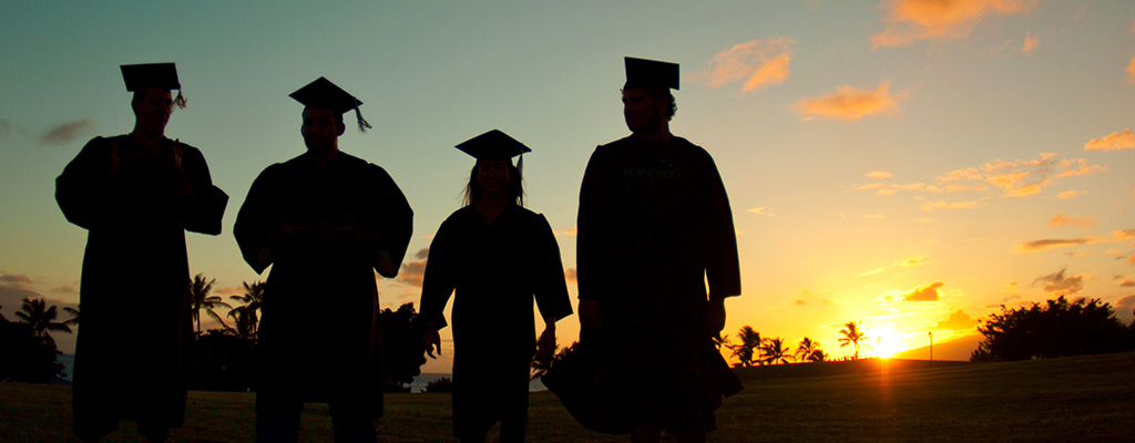 Silhouettes of four students in graduation regalia walking into the sunset