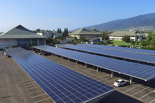 Maui College parking lot with large photo voltaic panels which also create shade for parked cars.
