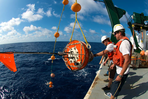 Researcher out on the ocean on a large vessel hauling up a buoy to collect data.
