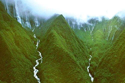 Koolau mountain range catching heavy raining clouds at the top ridges causing many waterfalls to pour down its sides collecting into rivers of of fresh water