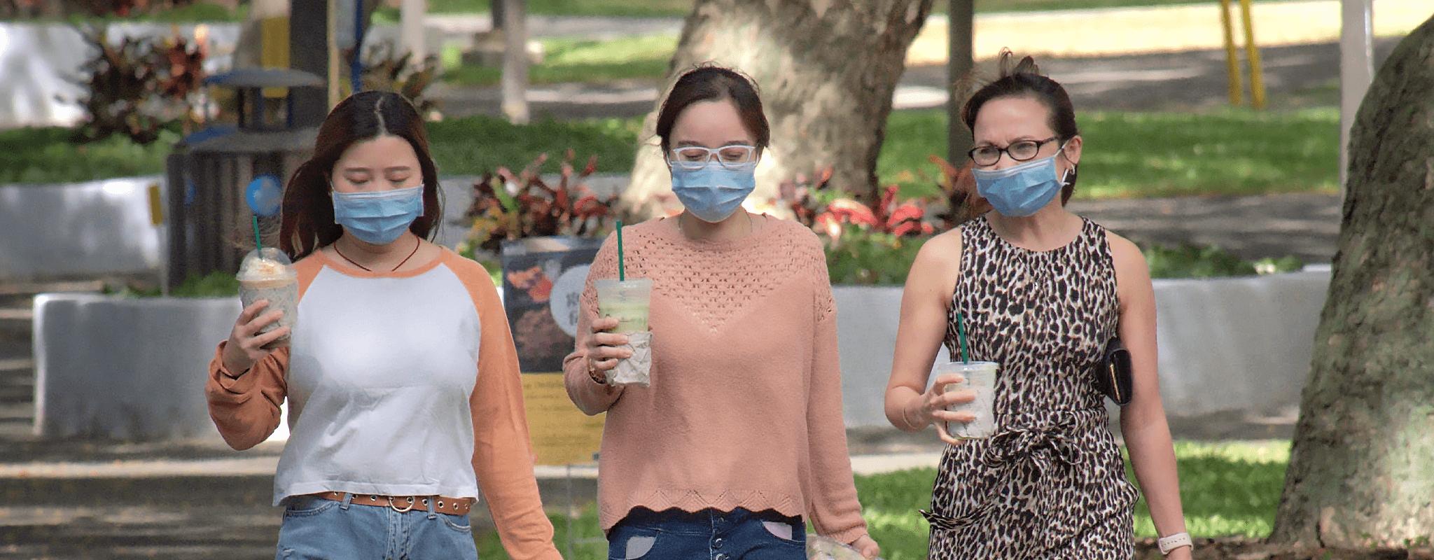Students wearing masks walking down the mall with breakfast drinks in hand